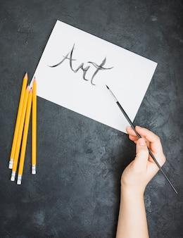 Menselijke hand geschreven kunsttekst op witte pagina met verfborstel over leioppervlakte