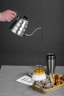 Menselijke hand giet koffie in een vat in een dunne stroom