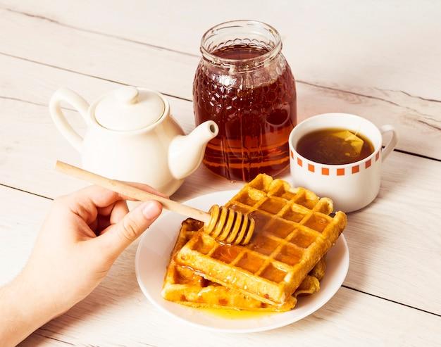 Menselijke hand gietende honing op belgische wafels die honingsdipper gebruiken
