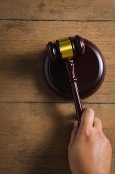 Menselijke hand greep hamer handvat op de houten tafel van bovenaanzicht