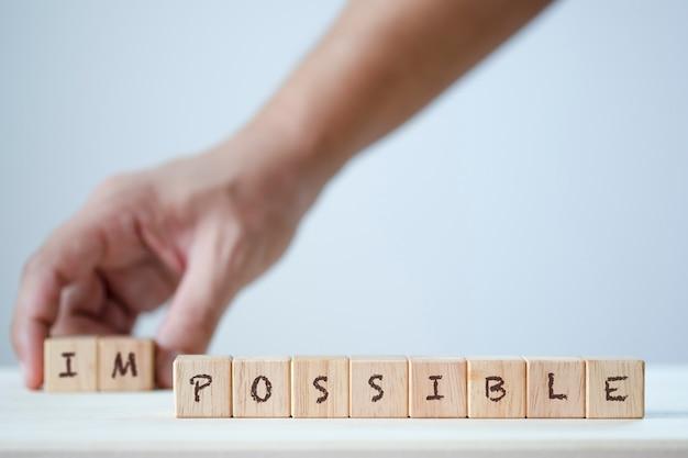 Menselijke hand houten kubus met formulering onmogelijk te verwijderen