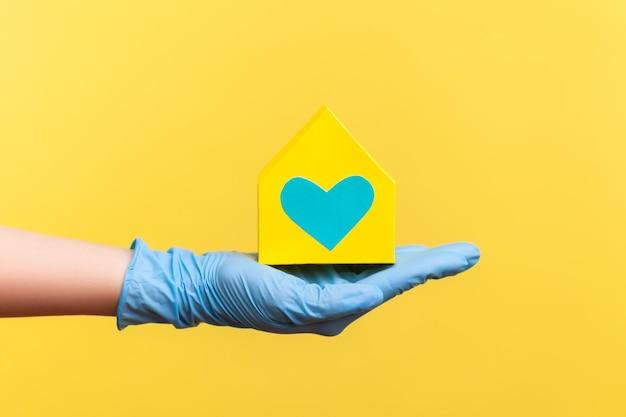 Menselijke hand in blauwe chirurgische handschoenen die de buitenkant van het gele papieren huis met liefde en zorg in de hand houden