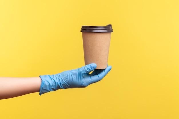 Menselijke hand in blauwe chirurgische handschoenen die een kop warme afhaalmaaltijdenmok in de hand houden en tonen.