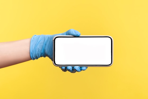 Menselijke hand in blauwe chirurgische handschoenen die een lege horizontale weergave van een smartphone vasthouden en tonen.