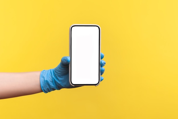 Menselijke hand in blauwe chirurgische handschoenen die een lege verticale weergave van een smartphone vasthouden en tonen.