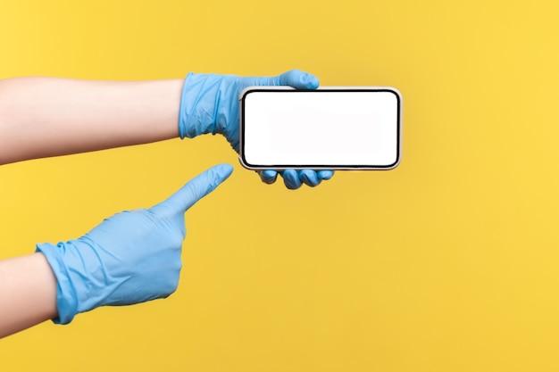 Menselijke hand in blauwe chirurgische handschoenen die een smartphone vasthouden en tonen en naar een leeg scherm wijzen.