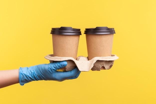Menselijke hand in blauwe chirurgische handschoenen die kopjes warme afhaalmaaltijden in de hand houden en tonen.