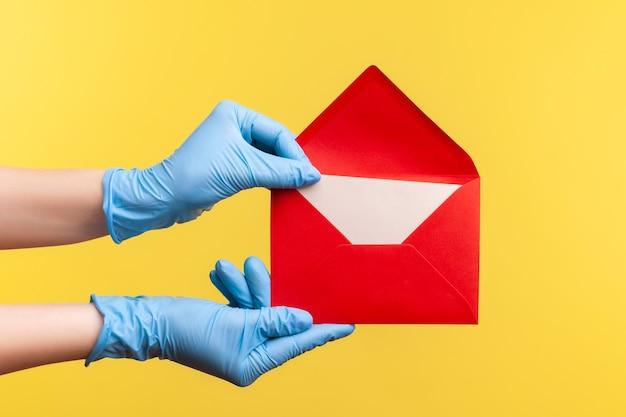 Menselijke hand in blauwe chirurgische handschoenen die rode geopende brievenenvelop vasthouden.
