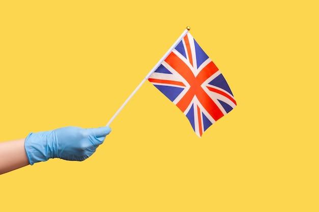 Menselijke hand in blauwe chirurgische handschoenen met vlag van een samenstellende eenheid van het verenigd koninkrijk.