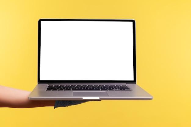 Menselijke hand in chirurgische handschoenen die een computerlaptop vasthouden en lege kopieerruimte op het beeldscherm tonen