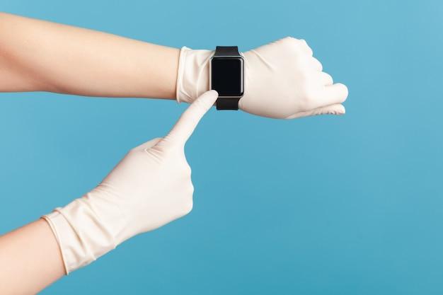 Menselijke hand in chirurgische handschoenen die het slimme horloge van de pols vasthouden en tonen en naar een leeg scherm wijzen.