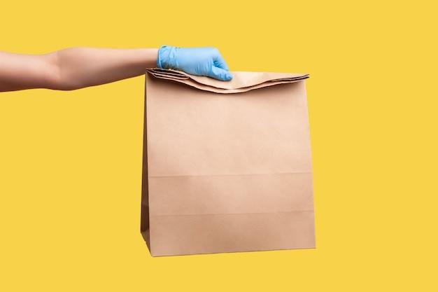Menselijke hand in chirurgische handschoenen met en ambachtelijk papieren pakket met voedsel. veilig voedselbezorgingsconcept