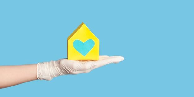 Menselijke hand in witte chirurgische handschoenen die de buitenkant van het gele papieren huis met liefde en zorg in de hand houden