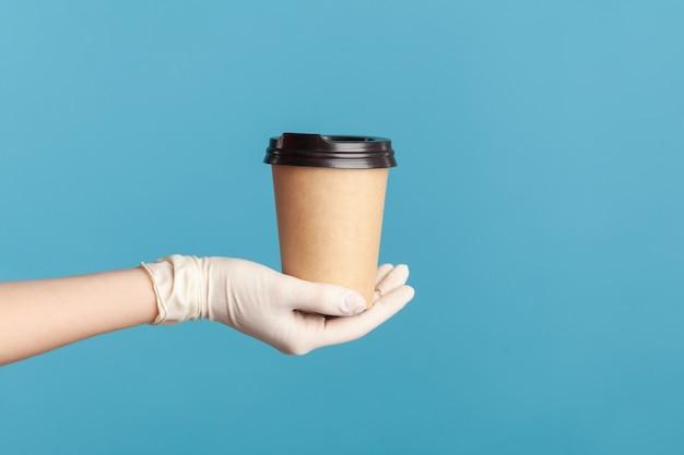 Menselijke hand in witte chirurgische handschoenen die een kop warme afhaalmaaltijdenmok in de hand houden en tonen.