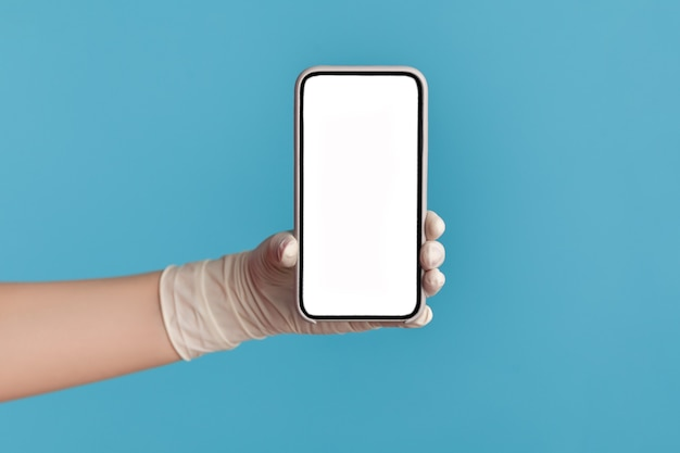 Menselijke hand in witte chirurgische handschoenen die een leeg scherm van een smartphone vasthouden en tonen.