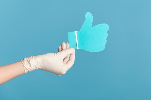 Menselijke hand in witte chirurgische handschoenen die een teken van een papieren vorm vasthouden en tonen.