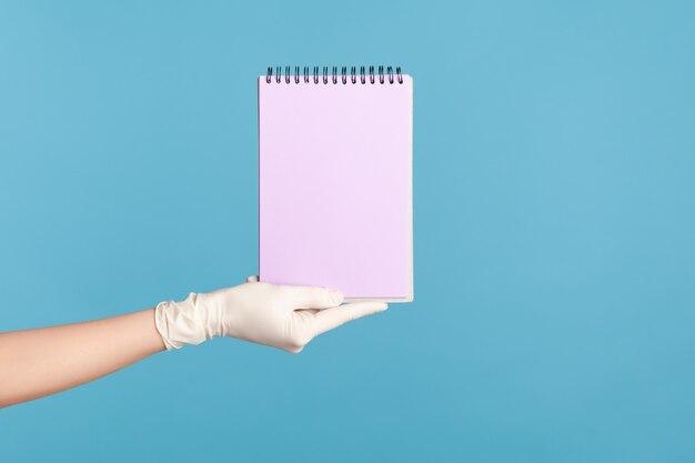 Menselijke hand in witte chirurgische handschoenen met paarse blocnote in de hand en met leeg papier.