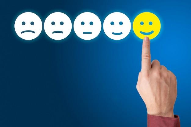 Menselijke hand is beoordeling met gelukkig pictogram. ranking en klanttevredenheid concept.