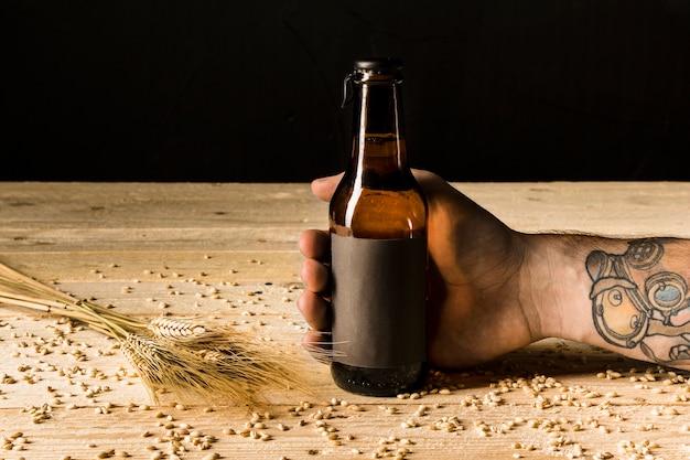 Menselijke hand met alcoholische fles met oren van tarwe op houten oppervlak