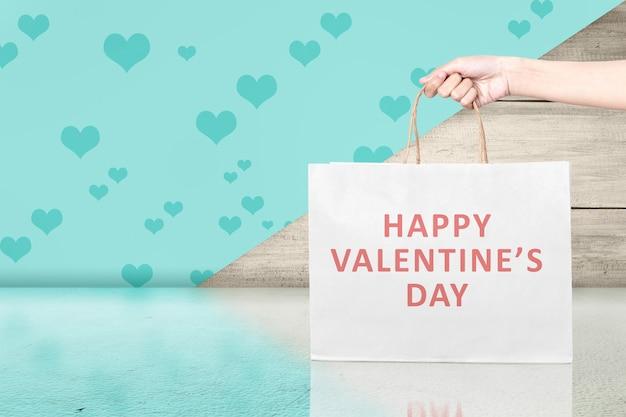 Menselijke hand met boodschappentassen met een gekleurde achtergrond. valentijnsdag