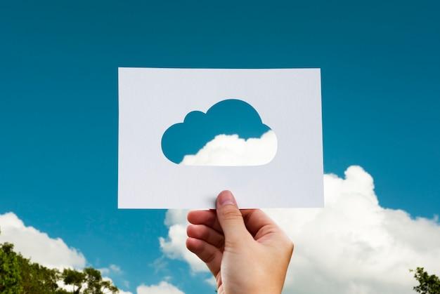 Menselijke hand met cloud geperforeerde papier vaartuigen in de natuur