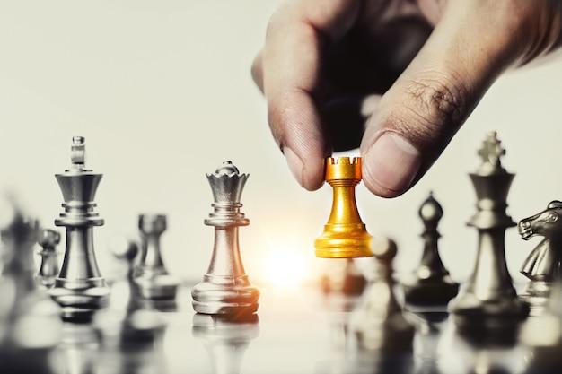 Menselijke hand met een gouden schaakstuk op schaakbord holding