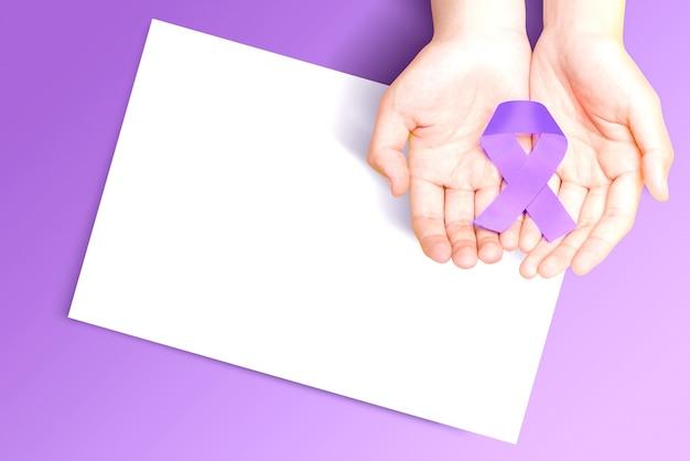 Menselijke hand met een paarse linten met leeg wit papier op een gekleurde achtergrond. wereldkankerdag concept. leeg witboek voor exemplaarruimte
