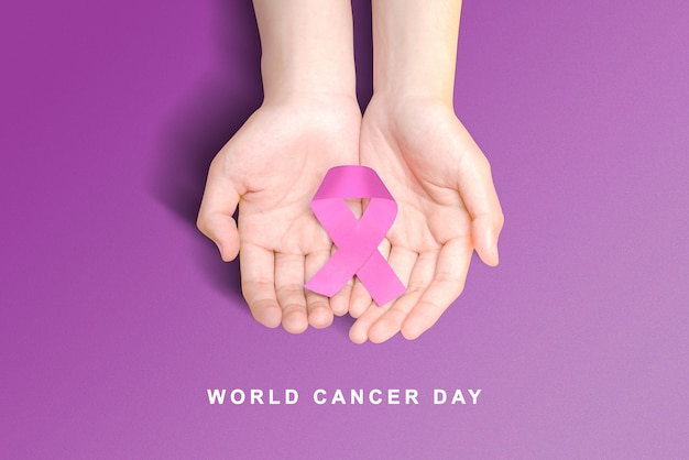 Menselijke hand met een paarse linten op een gekleurde achtergrond. wereldkankerdag concept