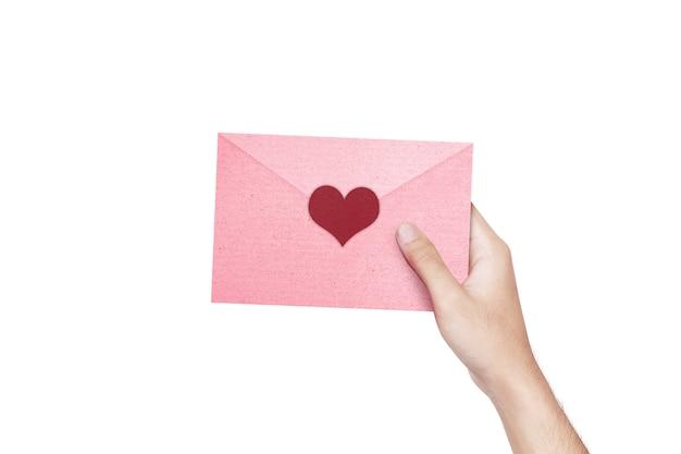 Menselijke hand met een roze envelop met hart geïsoleerd over witte muur