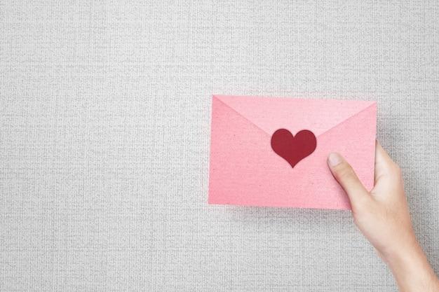 Menselijke hand met een roze envelop met hart met getextureerde muur