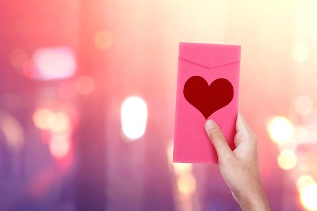 Menselijke hand met een roze envelop met hartvorm met wazig lichte muur. valentijnsdag