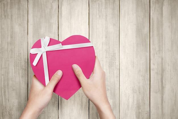 Menselijke hand met een roze geschenkdoos met wit lint en hartvorm met houten muur. valentijnsdag