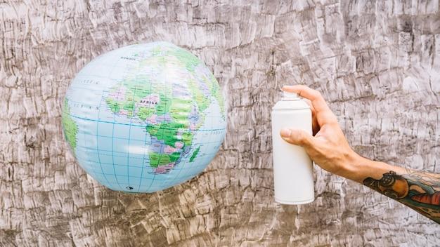 Menselijke hand met fles in de buurt van globe over houten achtergrond