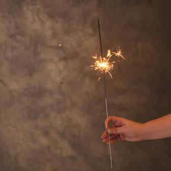 Menselijke hand met het vlammende licht van bengalen in mist