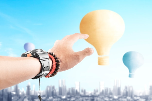 Menselijke hand met kleurrijke luchtballon vliegen met stadsgezicht achtergrond
