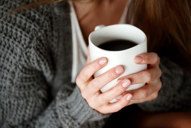 Menselijke hand met koffiemok