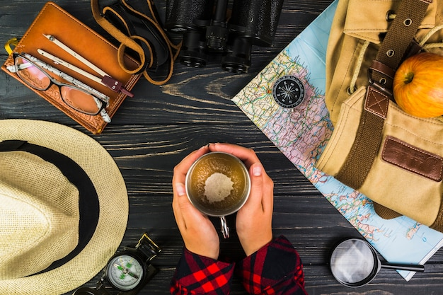Menselijke hand met kopje koffie omringd met verschillende reizende apparatuur
