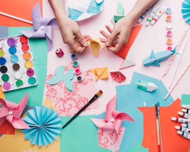 Menselijke hand met origami vogel over ambachtelijke product