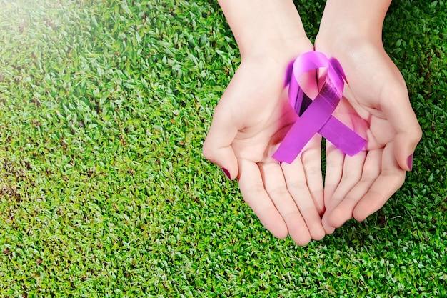 Menselijke hand met paars lint. wereldkankerdag concept