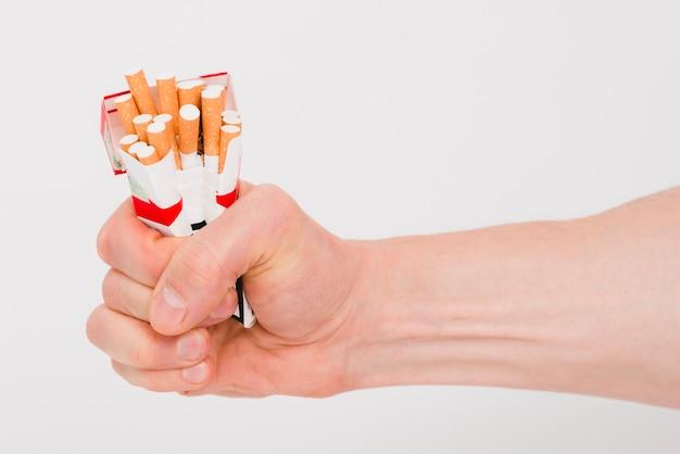 Menselijke hand met pakket van sigaretten