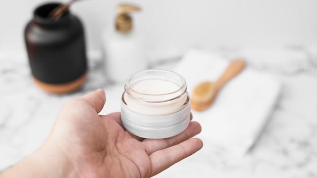 Menselijke hand met pot vochtinbrengende crème