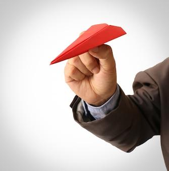 Menselijke hand met rode papieren vliegtuigje