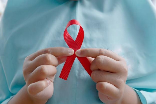 Menselijke hand met rood lint. wereldkankerdag concept