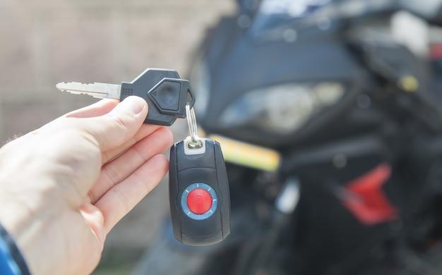 Menselijke hand met sleutels op de achtergrond van motorfiets levensstijl