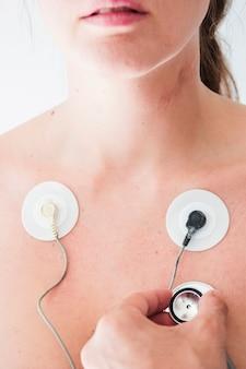 Menselijke hand met stethoscoop die ademhaling van vrouw controleert