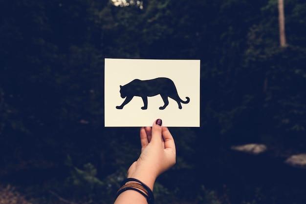 Menselijke hand met wild leven luipaard geperforeerd papier vaartuig in n