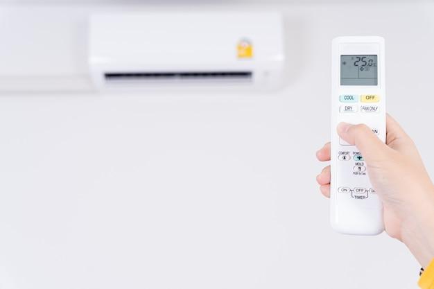 Menselijke hand met witte afstandsbediening om de temperatuur van de airconditioner aan te passen.
