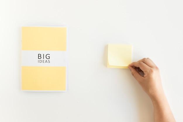 Menselijke hand met zelfklevende notitie naast grote ideeën dagboek