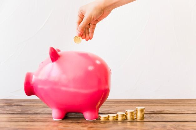 Menselijke hand munt invoegen in roze spaarpot