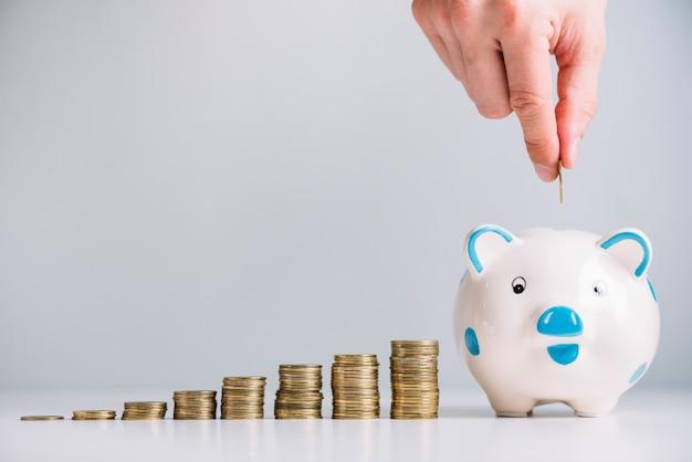 Menselijke hand munt invoegen in spaarpot